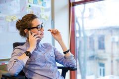 Ευτυχής επιχειρησιακή γυναίκα που μιλά στο τηλέφωνο κυττάρων στην αρχή Στοκ εικόνα με δικαίωμα ελεύθερης χρήσης