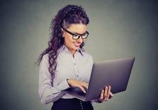Ευτυχής επιχειρησιακή γυναίκα που στέκεται χρησιμοποιώντας το φορητό προσωπικό υπολογιστή στοκ φωτογραφία