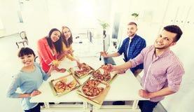 Ευτυχής επιχειρησιακή ομάδα που τρώει την πίτσα στην αρχή Στοκ Εικόνα
