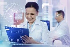 Ευτυχής εργαζόμενος εργαστηρίων που χαμογελά εξετάζοντας τις σημειώσεις της Στοκ Εικόνες