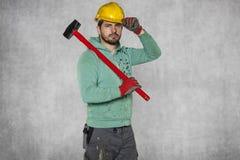 Ευτυχής εργαζόμενος με ένα σφυρί στον ώμο του και ένα κράνος στο χ του Στοκ φωτογραφία με δικαίωμα ελεύθερης χρήσης