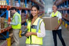Ευτυχής εργαζόμενος που θέτει και που χαμογελά στη κάμερα μπροστά από τους συναδέλφους της Στοκ Φωτογραφίες