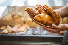 ευτυχής εργαζόμενος που κρατά ένα καλάθι croissant Στοκ Φωτογραφία