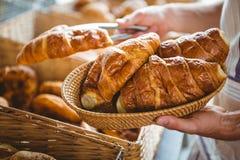 ευτυχής εργαζόμενος που κρατά ένα καλάθι croissant Στοκ εικόνα με δικαίωμα ελεύθερης χρήσης