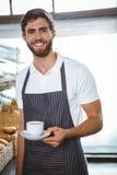 ευτυχής εργαζόμενος στην ποδιά που κρατά ένα φλιτζάνι του καφέ Στοκ φωτογραφία με δικαίωμα ελεύθερης χρήσης