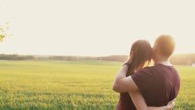 Ευτυχής ερωτευμένη στάση ανδρών και γυναικών σε έναν τομέα στο ηλιοβασίλεμα Αγκαλιάζουν και φιλούν, ήπια αφή μεταξύ τους Αργό MO απόθεμα βίντεο