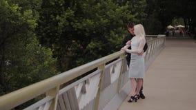 Ευτυχής ερωτευμένη στάση ζευγών στη γέφυρα σιδήρου στο πάρκο πόλεων και αγκάλιασμα απόθεμα βίντεο
