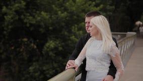 Ευτυχής ερωτευμένη στάση ζευγών στη γέφυρα σιδήρου στο πάρκο πόλεων και αγκάλιασμα φιλμ μικρού μήκους