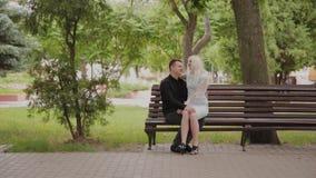 Ευτυχής ερωτευμένη συνεδρίαση ζευγών σε έναν πάγκο σε ένα πάρκο πόλεων φιλμ μικρού μήκους