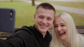 Ευτυχής ερωτευμένη συνεδρίαση ζευγών σε έναν πάγκο στο πάρκο και την παραγωγή πόλεων selfie στο τηλέφωνο φιλμ μικρού μήκους
