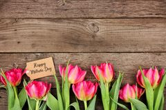 Ευτυχής ετικέττα ημέρας μητέρων με τα κατώτατα σύνορα των ρόδινων λουλουδιών σε ένα αγροτικό ξύλινο κλίμα στοκ φωτογραφίες με δικαίωμα ελεύθερης χρήσης