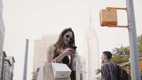 Ευτυχής ευρωπαϊκή γυναίκα ανεξάρτητος εργαζόμενος με τις τσάντες αγορών στα γυαλιά ηλίου που χαμογελά, χρησιμοποιώντας το smartph φιλμ μικρού μήκους
