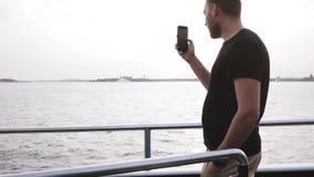 Ευτυχής ευρωπαϊκός αρσενικός ταξιδιώτης που κάνει ένα τηλεοπτικό smartphone χρησιμοποίησης απόθεμα βίντεο