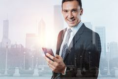 Ευτυχής ευχαριστημένος επιχειρηματίας που κρατά ένα smartphone στοκ εικόνα