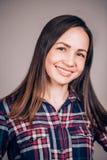 Ευτυχής εύθυμη νέα γυναίκα που φορά το πουκάμισο καρό που εξετάζει τη κάμερα με το χαρούμενο και γοητευτικό χαμόγελο κορίτσι σπου στοκ φωτογραφία με δικαίωμα ελεύθερης χρήσης