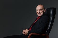 Ευτυχής εύθυμη συνεδρίαση επιχειρηματιών στην καρέκλα γραφείων και χαμόγελο Στοκ φωτογραφία με δικαίωμα ελεύθερης χρήσης