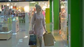 Ευτυχής εύθυμη ψωνίζοντας γυναίκα που περπατά στο κατάστημα με τις τσάντες εγγράφου φιλμ μικρού μήκους