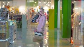 Ευτυχής εύθυμη ψωνίζοντας γυναίκα στο κατάστημα με τις τσάντες εγγράφου απόθεμα βίντεο