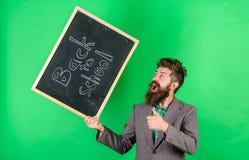 Ευτυχής εύθυμος δασκάλων συγχαίρει με την αρχή νέο σχολικό έτος Το γενειοφόρο άτομο δασκάλων κρατά τον πίνακα με στοκ εικόνες με δικαίωμα ελεύθερης χρήσης