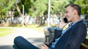 Ευτυχής εύθυμος επιχειρηματίας σε ένα κοστούμι που μιλά στη συνεδρίαση τηλεφωνικού χαμόγελου στον πάγκο σε ένα πάρκο την ηλιόλουσ φιλμ μικρού μήκους