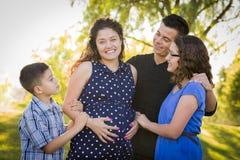 Ευτυχής ελκυστική ισπανική οικογένεια με την έγκυο μητέρα τους Outd στοκ εικόνα