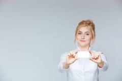 Ευτυχής ελκυστική νέα επιχειρηματίας που παρουσιάζει κενή επαγγελματική κάρτα Στοκ Φωτογραφία