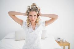 Ευτυχής ελκυστική ξανθή τοποθέτηση ρόλερ τρίχας φθοράς Στοκ Φωτογραφία