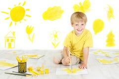 Ευτυχής ζωγραφική παιδιών με την κίτρινη βούρτσα χρώματος. Στοκ Εικόνες