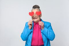 Ευτυχής ηλικίας γυναίκα που κρατά το κόκκινο μικρό σημάδι καρδιών δύο Στοκ φωτογραφία με δικαίωμα ελεύθερης χρήσης