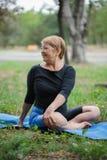 Ευτυχής ηλικιωμένη γυναίκα γιόγκας Χαμογελώντας ώριμη κυρία σε ένα χαλί σε ένα υπόβαθρο πάρκων υγιής τρόπος ζωής έννοιας διάστημα στοκ φωτογραφία με δικαίωμα ελεύθερης χρήσης