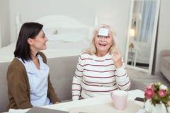Ευτυχής ηλικιωμένη γυναίκα και caregiver παίζοντας παιχνίδι στοκ φωτογραφίες