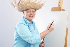 Ευτυχής ηλικιωμένη κυρία με τον καμβά και το πινέλο στοκ φωτογραφία με δικαίωμα ελεύθερης χρήσης