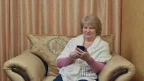 Ευτυχής ηλικιωμένη συνεδρίαση γυναικών σε μια άνετη καρέκλα που στηρίζεται στο σπίτι με μια συσκευή Ελκυστική χαμογελώντας κυρία  φιλμ μικρού μήκους