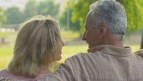 Ευτυχής ηλικιωμένος άνθρωπος που κάθεται στον πάγκο στο πάρκο, που μιλά και που αγκαλιάζει, πίσω άποψη απόθεμα βίντεο