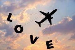Ευτυχής ημέρα βαλεντίνων, μύγα αεροπλάνων σκιαγραφιών στον ουρανό ηλιοβασιλέματος λυκόφατος με την αγάπη λέξης Στοκ Φωτογραφίες