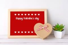 Ευτυχής ημέρα βαλεντίνων ` s στο ξύλινο κιβώτιο δώρων μορφής πινάκων και καρδιών επάνω Στοκ Εικόνες