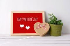 Ευτυχής ημέρα βαλεντίνων ` s στο ξύλινο κιβώτιο δώρων μορφής πινάκων και καρδιών επάνω Στοκ Φωτογραφία