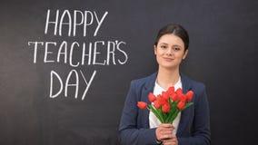 Ευτυχής ημέρα δασκάλων που γράφεται στον πίνακα, χαμογελώντας κυρία με τις τουλίπες που στέκονται πλησίον απόθεμα βίντεο