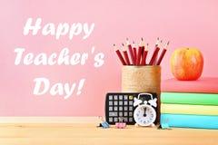 Ευτυχής ημέρα δασκάλων Προμήθειες σχολείου και γραφείων σε ένα ρόδινο υπόβαθρο πίσω σχολείο Στοκ εικόνες με δικαίωμα ελεύθερης χρήσης
