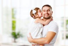 Ευτυχής ημέρα οικογενειών και του πατέρα Κόρη που φιλά και που αγκαλιάζει τον μπαμπά Στοκ Εικόνες