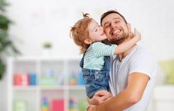 Ευτυχής ημέρα οικογενειών και του πατέρα Κόρη που φιλά και που αγκαλιάζει τον μπαμπά Στοκ Εικόνα