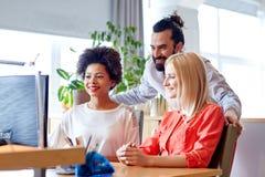 Ευτυχής δημιουργική ομάδα με τον υπολογιστή στην αρχή Στοκ φωτογραφίες με δικαίωμα ελεύθερης χρήσης