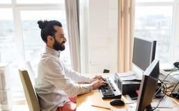 Ευτυχής δημιουργικός εργαζόμενος γραφείων αρσενικών με τον υπολογιστή Στοκ Εικόνα