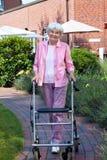 Ευτυχής ηλικιωμένη γυναίκα που χρησιμοποιεί μια ενίσχυση περπατήματος στοκ φωτογραφίες