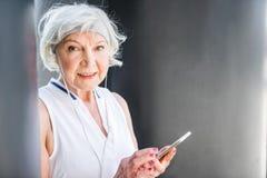 Ευτυχής ηλικιωμένη κυρία που χρησιμοποιεί το κινητό τηλέφωνο για την επικοινωνία υπαίθρια στοκ εικόνες με δικαίωμα ελεύθερης χρήσης