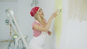 Ευτυχής θηλυκή βυθίζοντας βούρτσα στο χρώμα τοίχων απόθεμα βίντεο