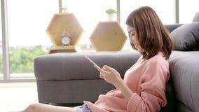 Ευτυχής θηλυκή ταμπλέτα χρήσης για, την ανάγνωση, την προσοχή τηλεοπτικές και το σερφ on-line στο σπίτι Έννοια γυναικών τρόπου ζω απόθεμα βίντεο