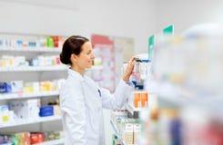 Ευτυχής θηλυκός αποθηκάριος με το φάρμακο στο φαρμακείο στοκ φωτογραφίες με δικαίωμα ελεύθερης χρήσης