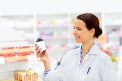 Ευτυχής θηλυκός αποθηκάριος με το φάρμακο στο φαρμακείο στοκ φωτογραφία