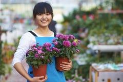 Ευτυχής θηλυκός ασιατικός ανθοκόμος που εξετάζει το χαμόγελο καμερών στοκ εικόνες